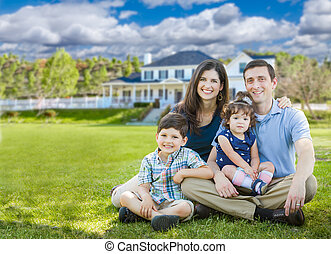 Happy Young Family With Children Outdoors In Front of Beautiful Custom Home.