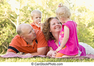 Happy Young Family with Cute Twins in Park