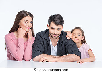 Happy young family with one child looking at camera on white