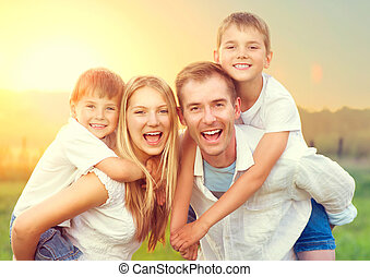 Happy young family with two children enjoying nature outdoors