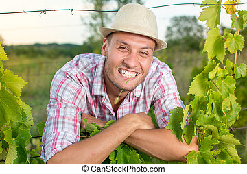 Happy young farmer at the vineyard