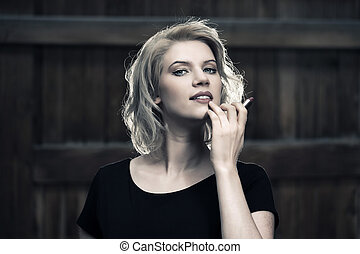 Happy young fashion blond woman holding a lipstick