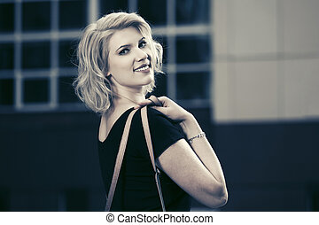Happy young fashion blond woman in black dress walking on city street