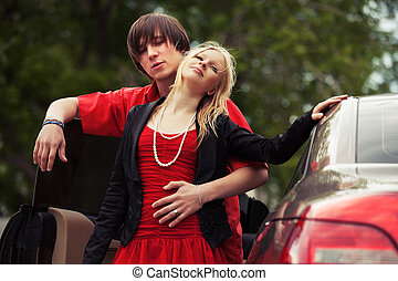 Happy young fashion couple in love by new car