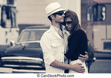 Happy young fashion couple in love embracing next to vintage car