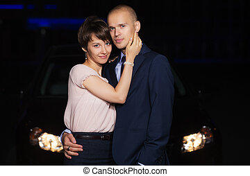 Happy young fashion couple in love next to car at night
