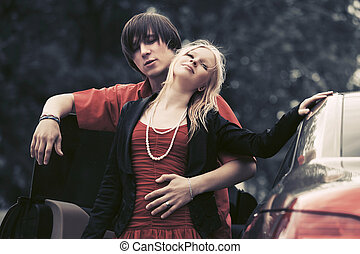 Happy young fashion couple in love outside a car