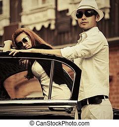 Happy young fashion couple leaning on vintage car