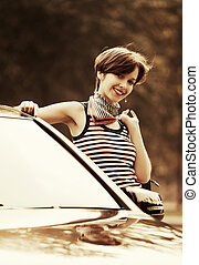 Happy young fashion woman at the car