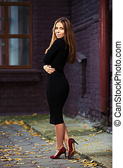 Happy young fashion woman in black dress at the brick wall