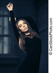 Happy young fashion woman in black dress walking in city street