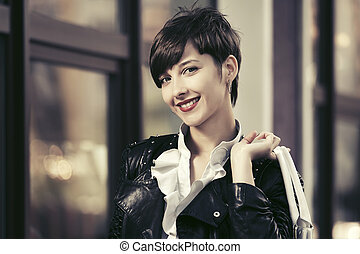 Happy young fashion woman in leather jacket with handbag