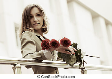 Happy young fashion woman with bouquet of red roses