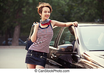 Happy young fashion woman with handbag next to her car