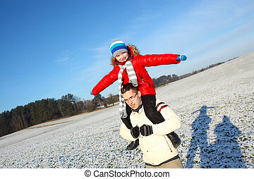 happy young father and his little son spending time outdoor in winter park. Son sits on his father's shoulders and having fun