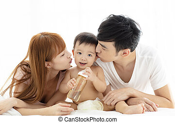 happy young father and mother kissing baby