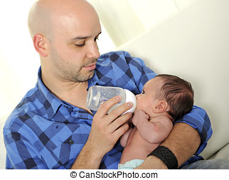 young father feeding newborn baby with milk bottle on couch at home