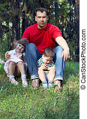 Happy young father in red t-shirt with two kids