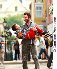 Happy young father playing with his son on background of the city streets