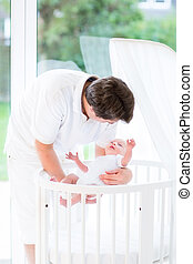 Happy young father putting his newborn baby in a white crib at a