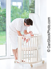 Happy young father putting his smiling newborn baby into a white