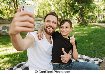 Happy young father sitting with his little son make selfie by mobile phone