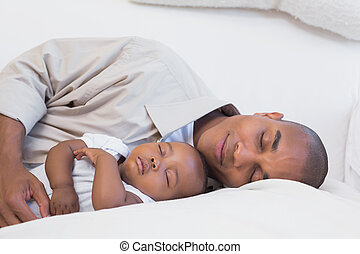 Happy young father with baby son on couch
