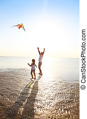 Happy young father with daughter with flying a kite on the beach
