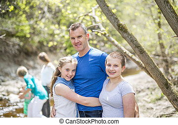 Happy young father with daughters outdoors