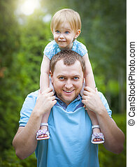 Happy young father with little daughter outdoors