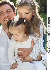 Happy young father with two little daughters