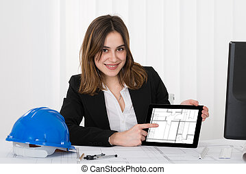 Female Architect Pointing At Blueprint On Digital Tablet