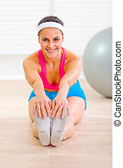 Happy young female doing exercises on floor at home