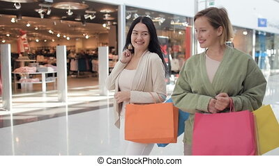 Happy young female friends walking with shopping bags in the mall