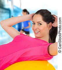 Happy young fitness woman on punch ball