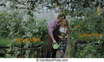 Happy young florist family in apron have fun during working in greenhouse. Attractive man embrace and kiss his wife
