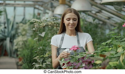 Happy young florist family in apron working in greenhouse. Attractive man embrace and kiss his wife while she watering flowers with garden spray