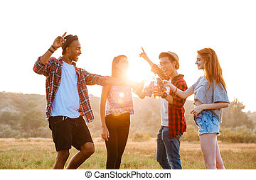 Happy young friends drinking beer and soda outdoors