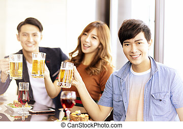 happy young friends drinking beer in  restaurant.