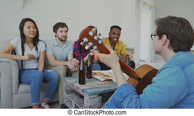 Happy young friends have party playing guitar and singing together at home