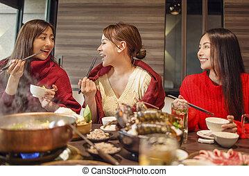 happy young friends  having fun in hot pot restaurant