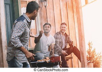 happy young friends making barbecue on porch with back light