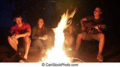 Happy young friends sitting near the campfire and singing songs with a guitar