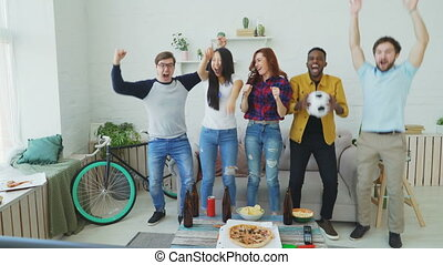 Happy young friends watching sports game on TV jumping and celebrating victory of favourite team at home