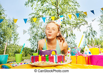 Happy young girl blowing candles on birthday cake
