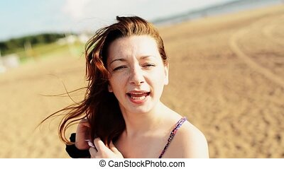 Happy young girl dancing on beach smile in camera. Sunny...