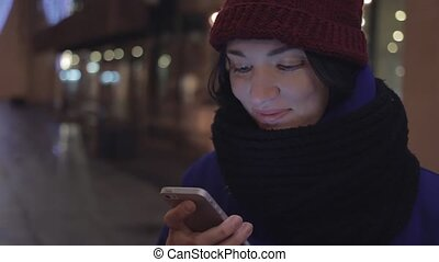 Happy young girl dressed in jacket and knitted scarf laughing using smartphone