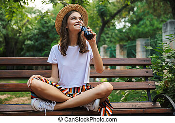 Happy young girl drinking from a bottle with fizzy drink