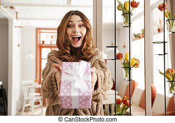Happy young girl giving a present box while standing
