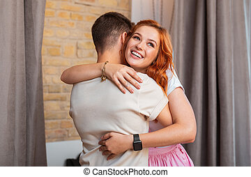 Happy young girl hugging her young boyfriend and smiling cheerfully